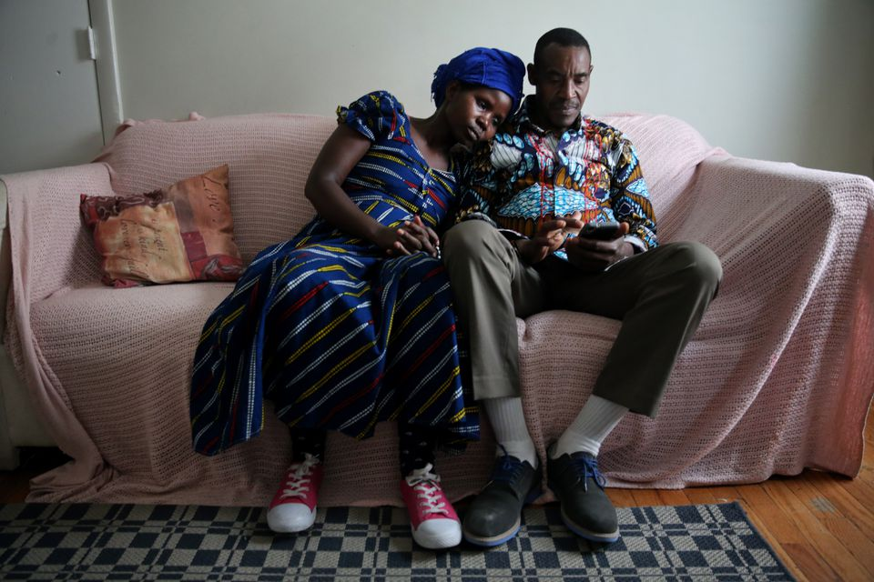 Vanisi Uzamukunda, left, and her husband Sendegeya Bayavuge relaxed on the couch at their home in Lowell.