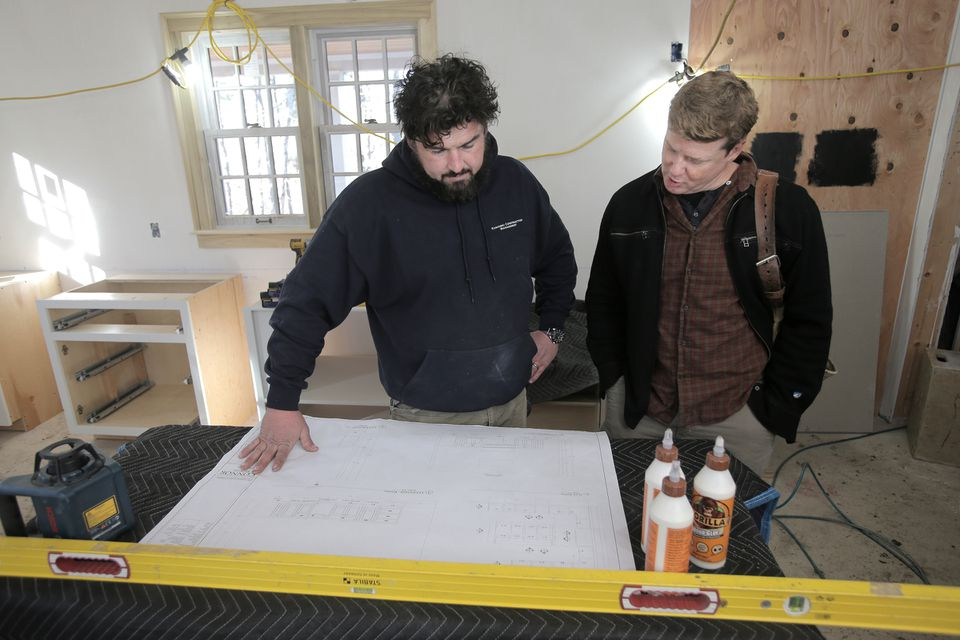 O'Connor (right) and Kaminski, whose company, Kaminski Construction Management of Newburyport, served as the builder and general contractor, look over blueprints during a rehearsal before a take. With an off-center entry, the new Essex house is an informal version of the early 19th-century Federal style. It has four bedrooms and three full and two half baths.