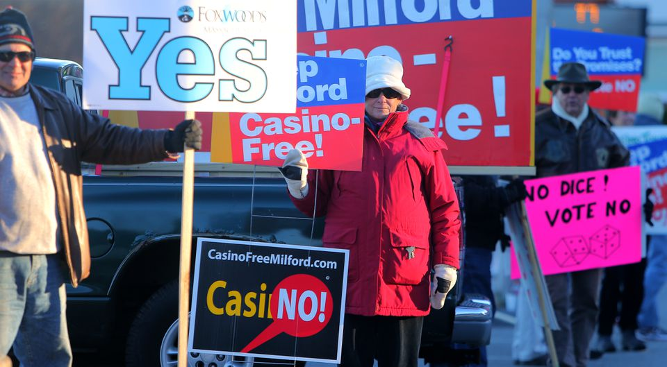 Guy Romano (left) and Nancy Wojick (center) held signs opposing a casino in Milford.