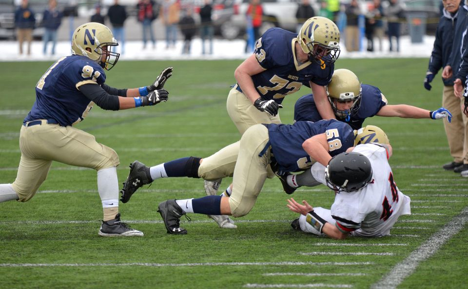 Needham players bring down Wellesley's TJ Noonan in the first quarter of Thursday's game.