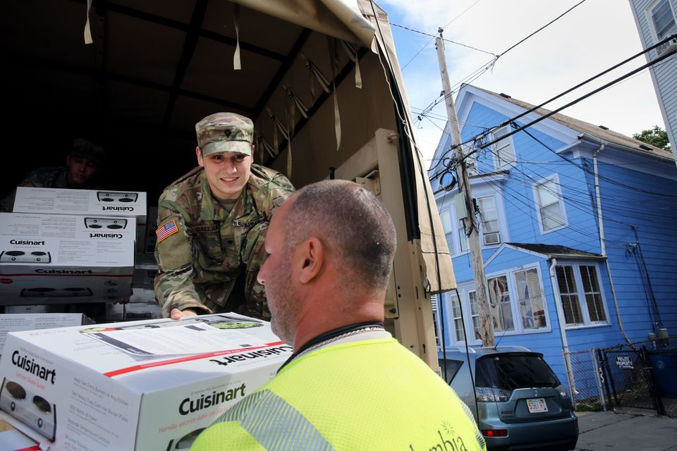 Specialist Matthew Gallen of the Massachusetts Army National Guard helped distribute hot plates to residents on Springfield Street in South Lawrence on Saturday.