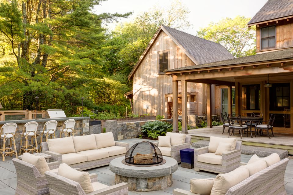 Comfy outdoor furniture surrounds a built-in fire pit, which is made from the same granite blocks as the nearby wall and topped with bluestone. Echoing the paving material used in the front of the house, the back patio was constructed with select bluestone from New York. Long granite slabs form steps to the covered porch that wraps around the house.