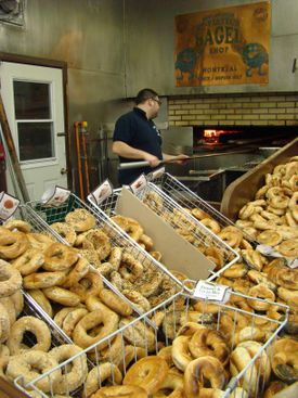 Montreal bagels are hand-rolled, boiled in honey-flavored water, and baked in a wood-fired oven (shown here: St-Viateur Bagel).