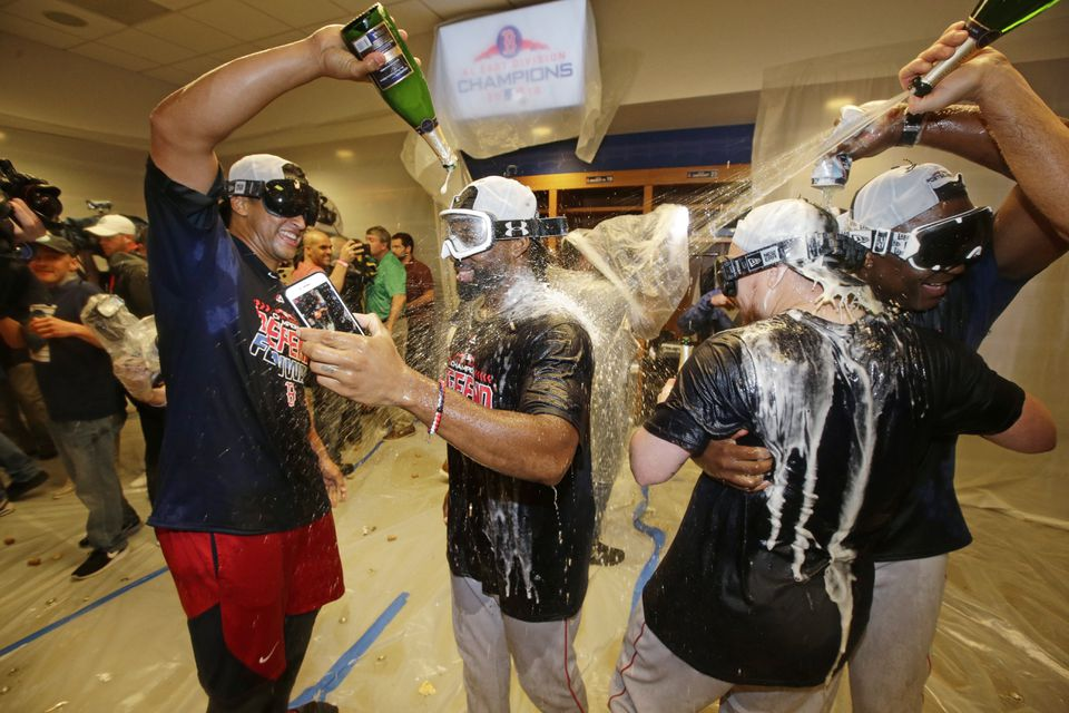 Jackie Bradley Jr., (center), William Cuevas (left) and Christian Vazquez (second from right) can't get enough champagne as they celebrate the Red Sox' AL East crown.