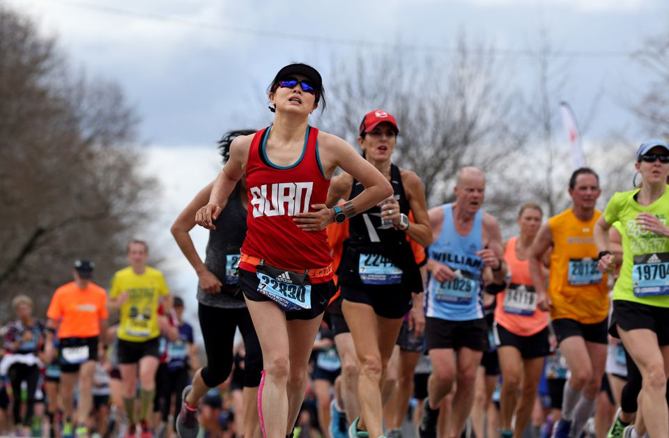 Shuhuan Yu struggles as she and other runners reach the top of Heartbreak Hill.