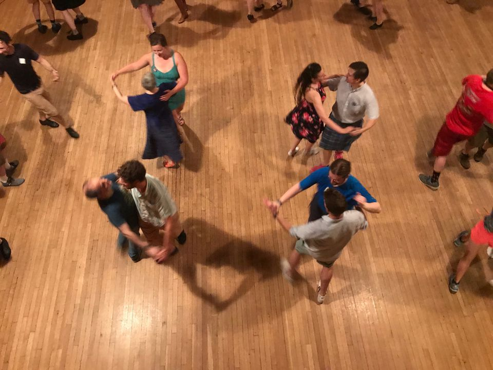 Dancers moved, following the instructions of a caller, as a folk band played.