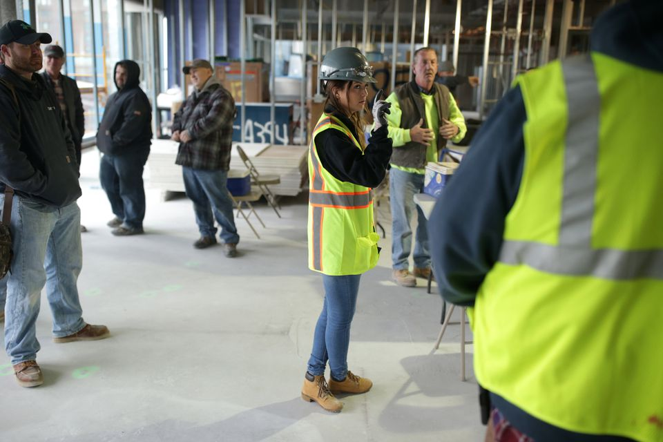 """Assistant project manager Danielle Weiler leads a """"toolbox talk,"""" recapping the day's activities at the Cambridge laboratory project."""