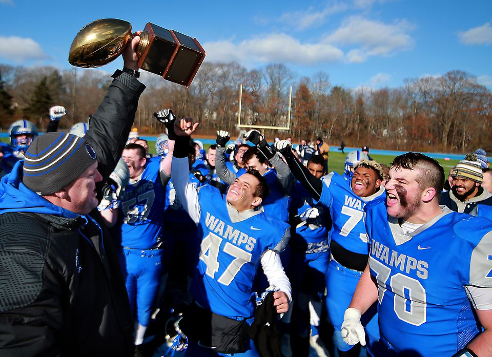 Braintree coach Brian Chamberlain hoists up the trophy as Billy Silvia (47) and his teammates look on after defeating Milton.