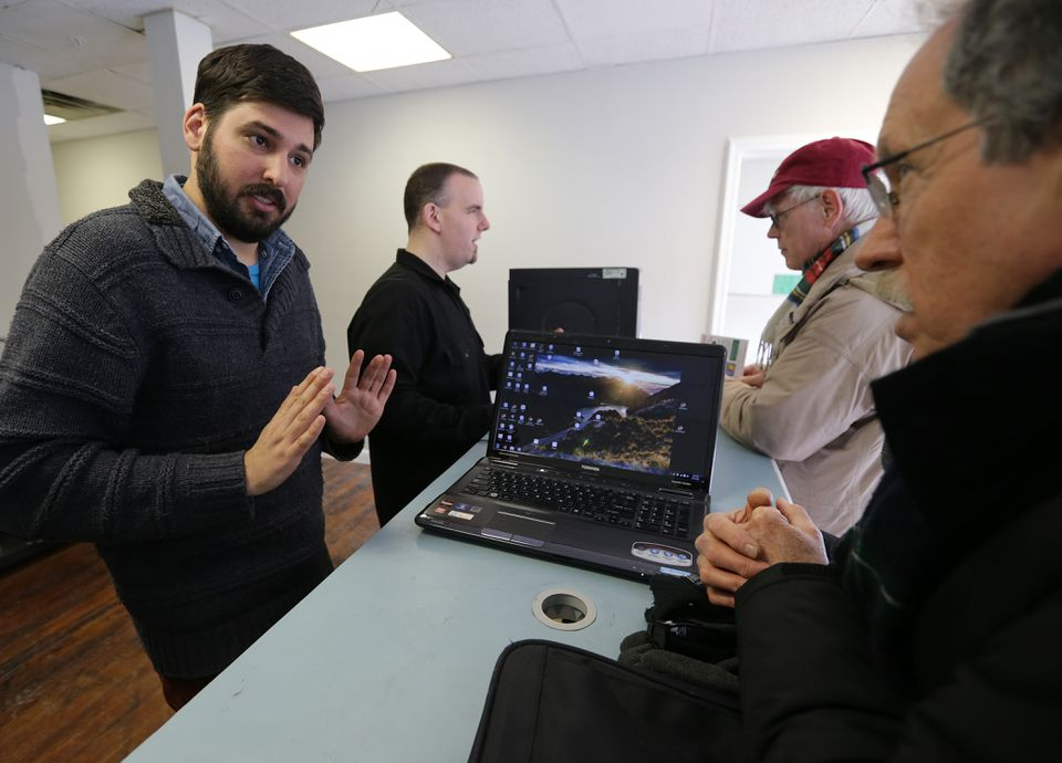 At Boston TechCollective in Somerville, (from left) Yochai Gal and Charlie Hoover assist customers Pat Hanlon and Brian Merrick with computer issues.