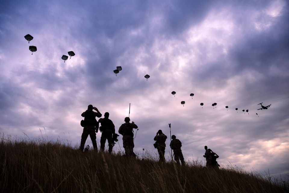 "Paratroopers drop out of a US Air Force Hercules during the ""Swift Response 17"" joint airborne military exercise."
