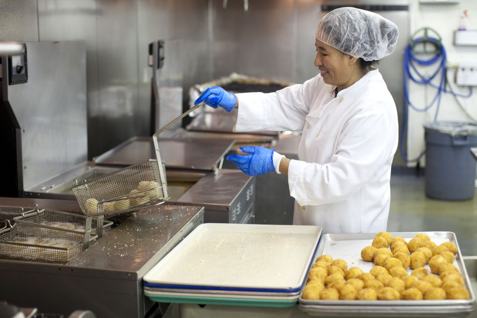 Ngawng Sangmo fried arancini balls in canola oil at the Whole Foods facility in Everett, which uses a new system of recycling oil.