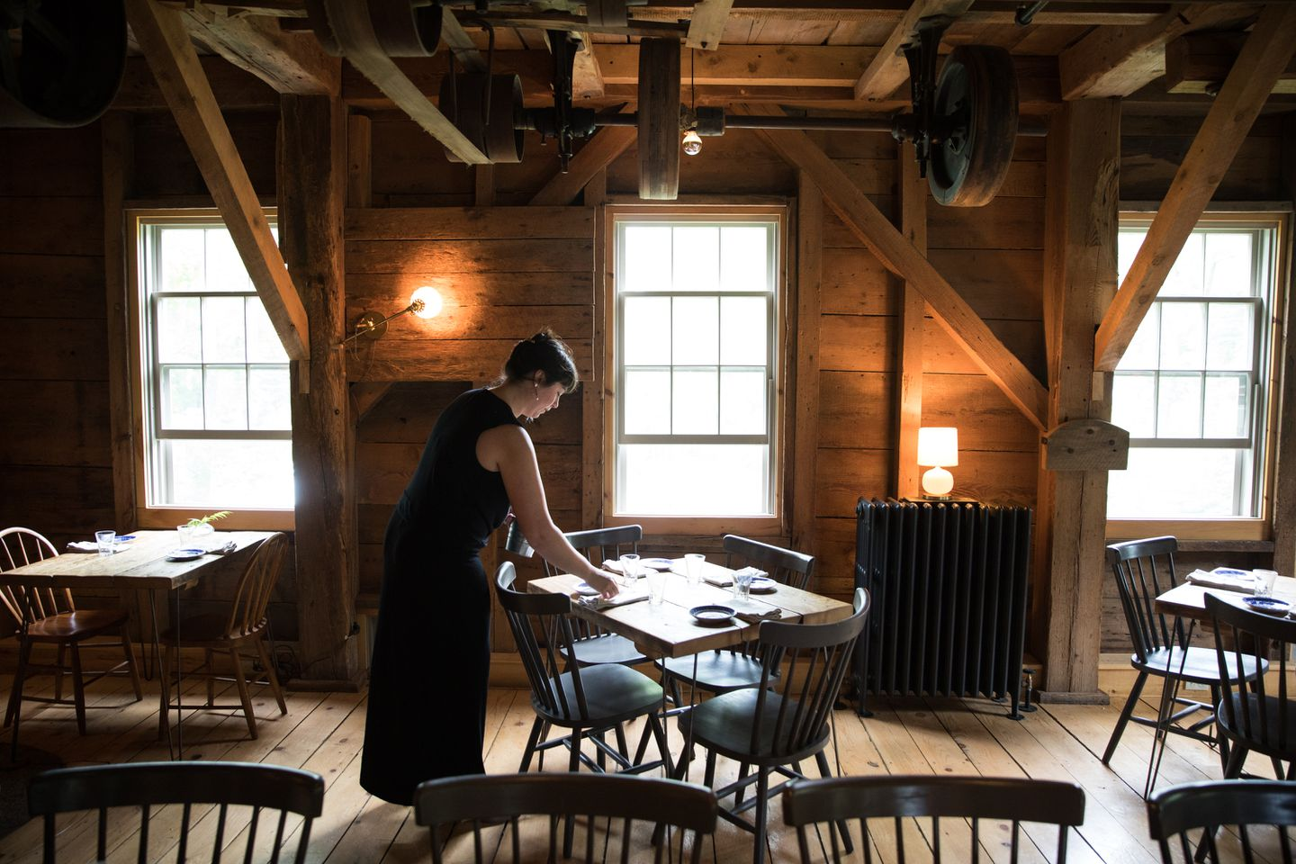 Lauren Crichton, a server at the Lost Kitchen, sets up the dining room for the evening meal.