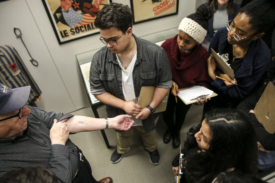 On a visit to the International Museum of World War II, Arbeiter shows  students from Malden  the identification number  tattooed on his arm while he was at Auschwitz.