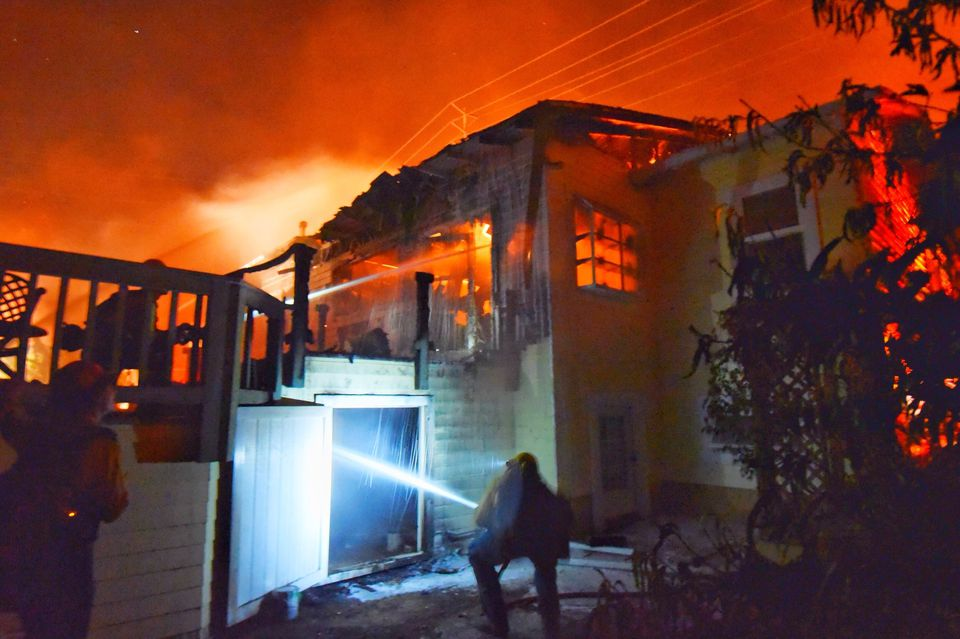 Firefighters doused flames at a home in Goleta, California on Friday.