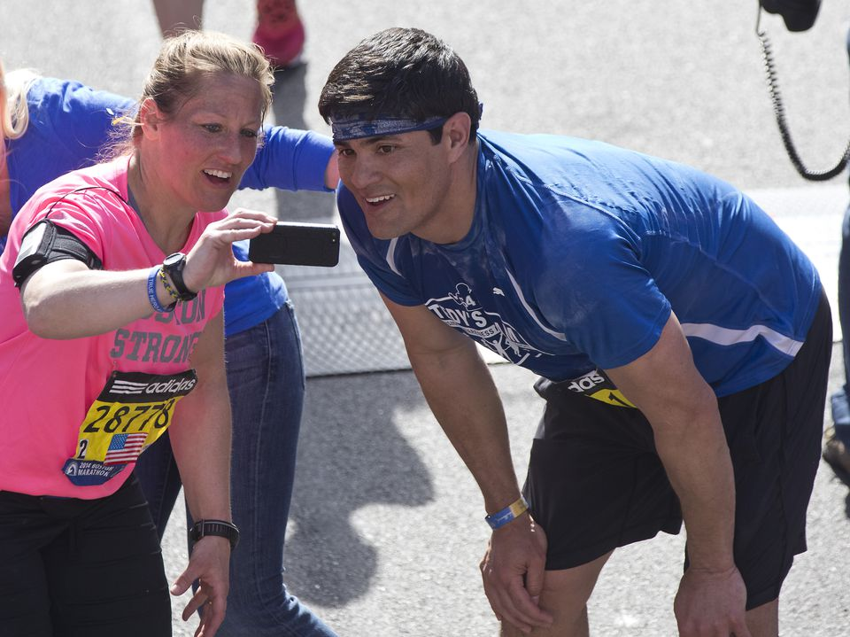 Tedy Bruschi posing for a selfie with a woman after finishing the 2014 Boston Marathon.