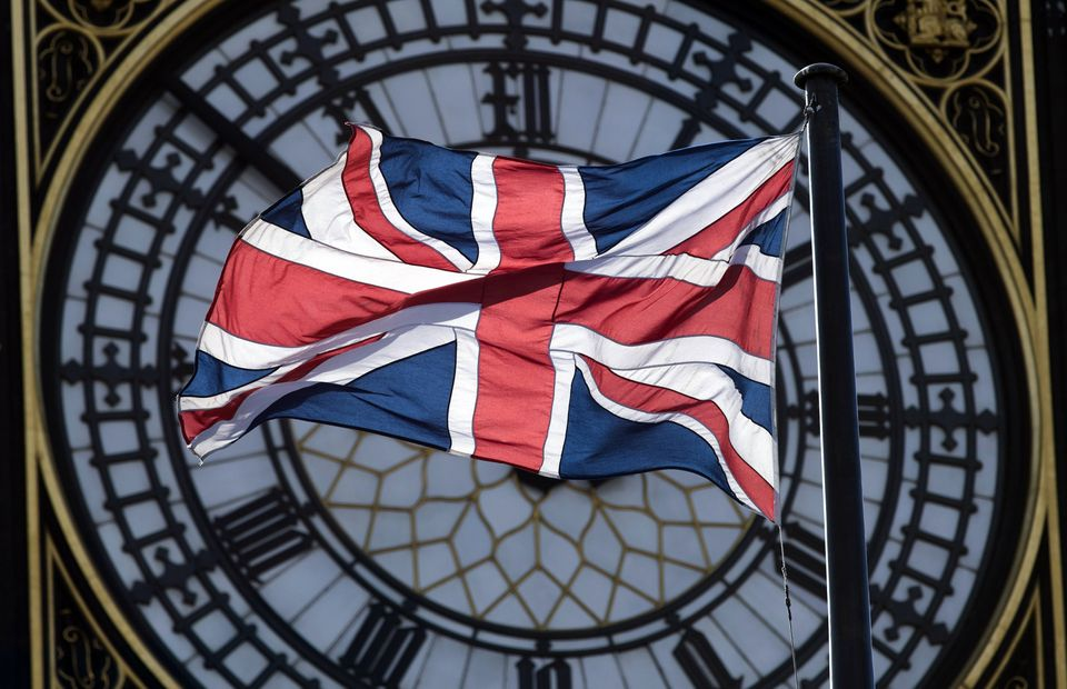 A Union flag on display in front of the clock on the Elizabeth tower at the Houses of Parliament in London.