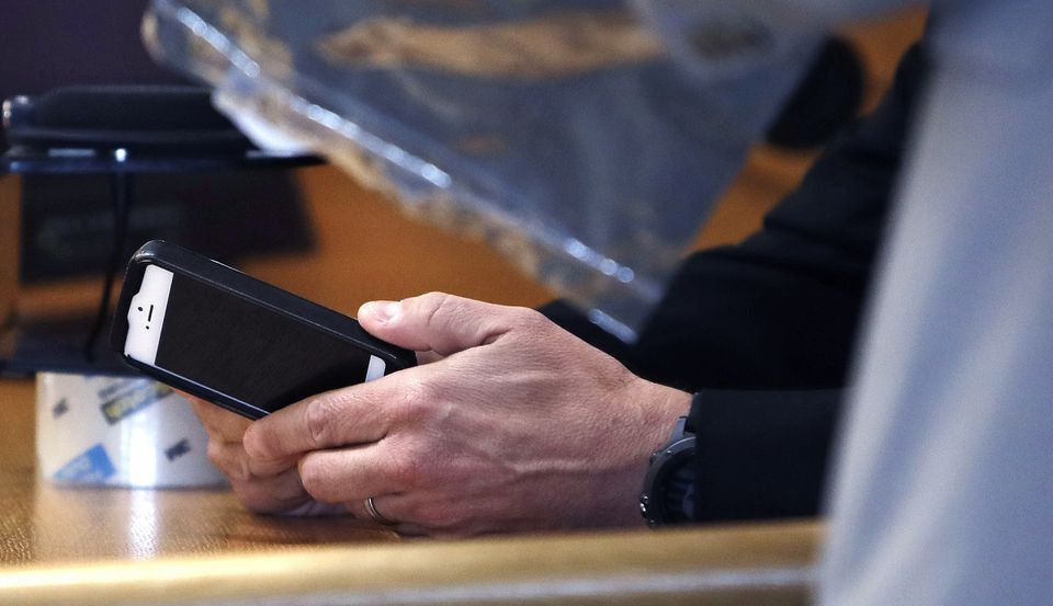 Massachusetts State Police Sgt. Michael Bates held an iPhone, which belonged to Conrad Roy III, while on the witness stand during the trial of Michelle Carter on Thursday.