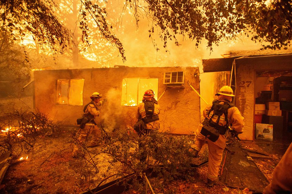 Firefighters push down a wall while battling against a burning apartment complex in Paradise, north of Sacramento, Calif., on Friday.