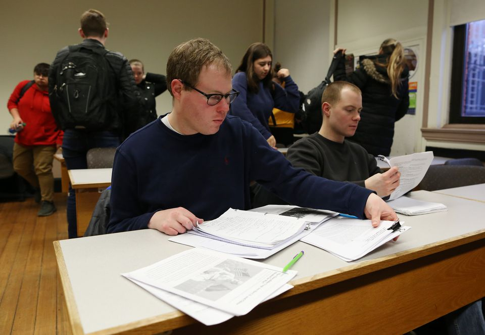 Johan Rijk (left) sat with his brother, Matt, who took notes for him in a class at Framingham State University last month. Johan suffered a stroke in 2010, when he was a junior, that paralyzed him.