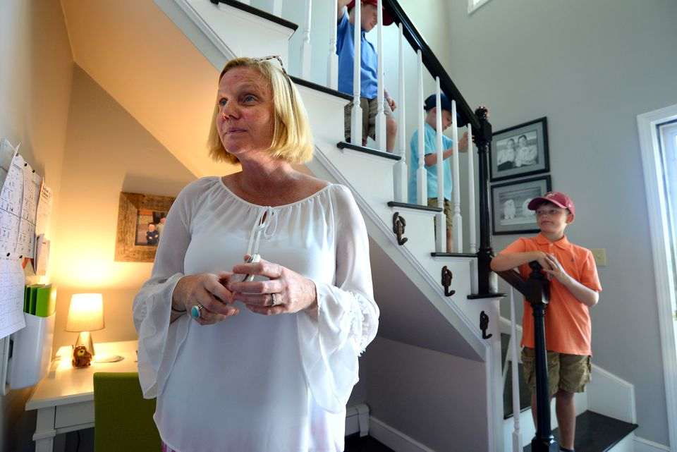Lisa Blake, a professional organizer, stands next to her Command Central space in the corner of the staircase of her Scituate home. Her sons on the stairs (from left): Wyatt Maldonis, his twin Hunter, 8, Mason, 9.