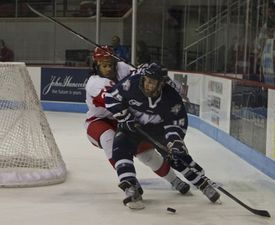 Yasin Cisse of BU attempts to separate the puck from UNH's Brett Kostolansky during the third period at Agganis Arena.