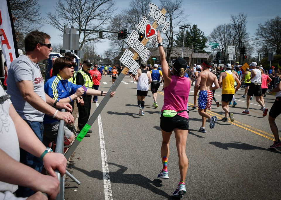 """A runner tapped a sign to celebrate climbing """"Heartbreak Hill"""" during the running of the 120th Boston Marathon in Newton on April 18, 2016."""