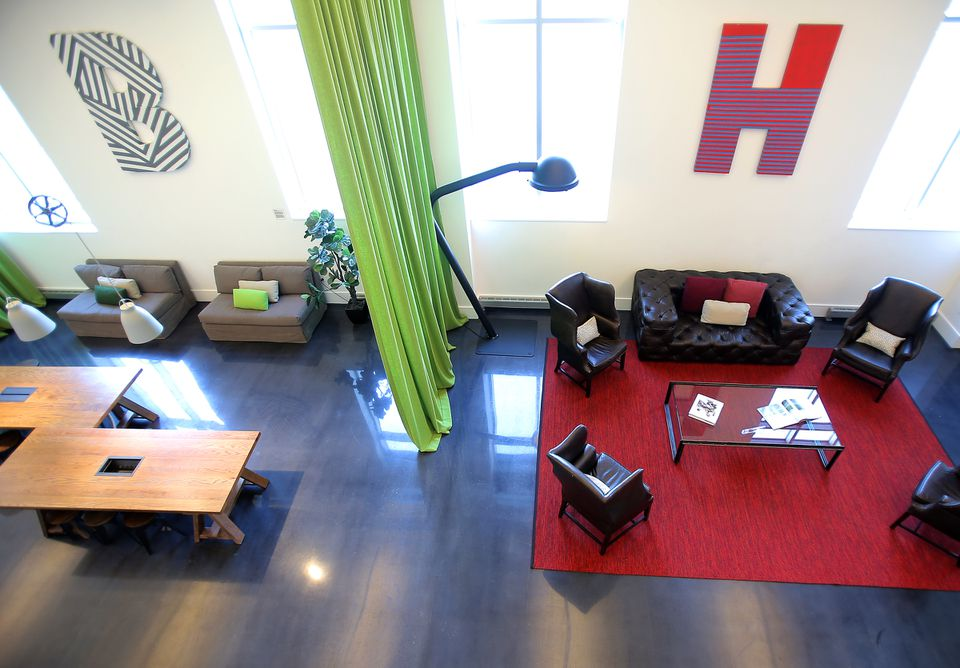 """A common area with the letters """"B'' and """"H'' pays homage to the site's old tenant, the Boston Herald."""