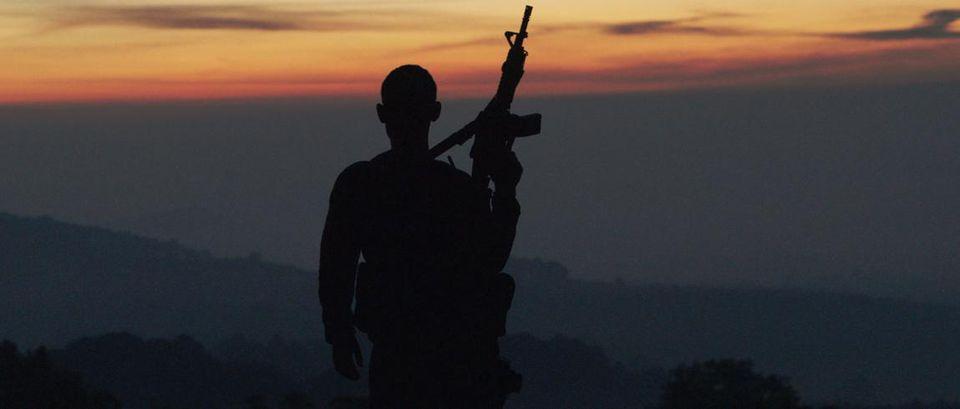 "Autodefensas member standing guard in Michoa-cán, Mexico, from Matthew Heineman's ""Cartel Land."""